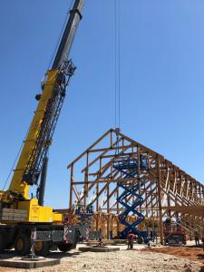 large crane raising trusses for timber frame building