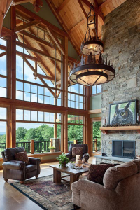 Photo of living room featuring timber encased windows and stacked stone fireplace