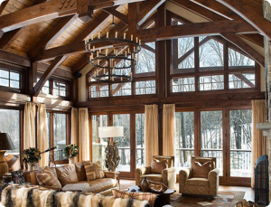 Photo of living room with timber trusses, beams and windows