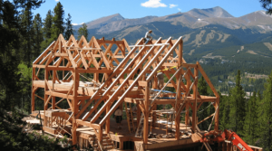 Timber frame home under construction surrounded by mountains